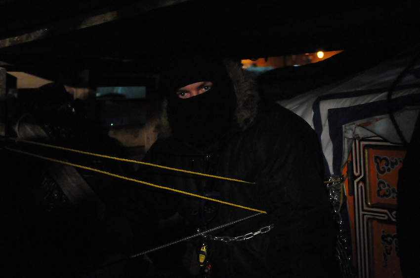 Night of November 21, 2011, one of two unidentified masked protesters barricaded against a yurt with packing crates and awaiting police at St. James Park.  This following the decision handed down this morning by Ontario Superior Court judge David Brown, upholding the Occupy Toronto tent camp eviction.