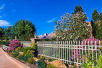 A home with beautiful flowers and lush greenery in Springdale, Utah (with the rock formations of Zion National Park in the background).