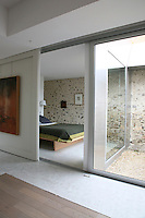 A system of sliding screens on hidden metal rails acts as a door and room dividers