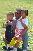 Father age 25 holding kids ages 6 and 3. In the Heart of the Beast May Day Festival and Parade St Paul  Minnesota USA