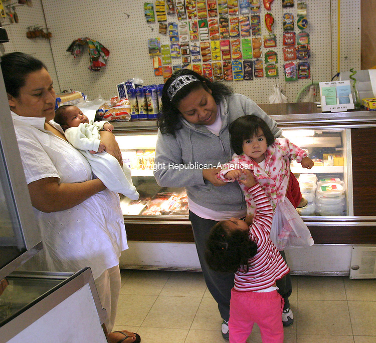 WATERBURY, CT 10/24/07- 102407BZ01- Paula Mendoza, left, holding her duaghter Paola Mendoza, watches as her daughter Susana Mendoza, 1-year-old, plays with Brittany Espina, 1-year-old, and her mother Lorena Espina, inside Los Arcos market the Mendoza's own on South Main Street in Waterbury Wednesday.<br /> Jamison C. Bazinet Republican-American