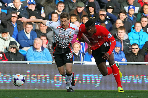 22.03.2014  Cardiff, Wales. Wilfried Zaha of Cardiff City and Jon Flanagan of Liverpool  in action during the Premier League game between Cardiff City and Liverpool from Cardiff City Stadium.