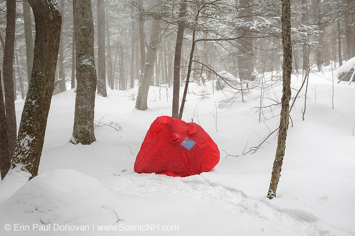 A hiker takes shelter inside a Bothy 2 during a snow storm in the White Mountains of New Hampshire USA. The Bothy 2 is a light-weight two man emergency shelter made by Terra Nova Equipment.