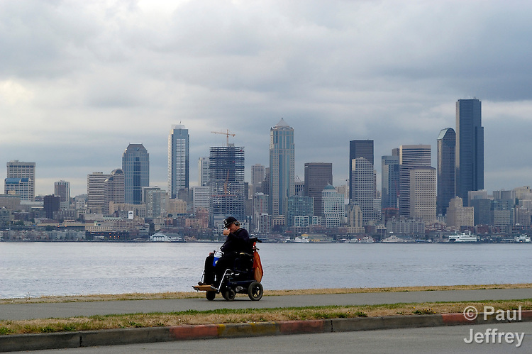 A man in a wheelchair navigates along the edge of Puget Sound in Seattle, Washington.