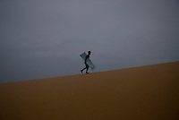 A Vietnamese boy walks the sand dunes looking for tourists to sell a sliding ride down the massive dunes in Mui Ne.  Mui Ne is famous for its red and white sand dunes.