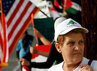 "Samira Shuhaib, a Lebanese-American for 20years, takes part in a rally promoting the safety of civilians in Lebanon on Saturday, July 29, 2006.  A crowd of several hundred gathered  on Brookhurst Street in Anaheim, Calif.  Shuhaib, who still has family in Lebanon, puts partial blame on U.S. foreign policy for putting Lebanese civilians in danger.  However, she still feels an affinity for the country.  ""I have lived in both.  I love both.  So, what can I do?"" says Shuhaib. (Photo by Bryce Yukio Adolphson/Brooks Institute of Photography, ©2006)"