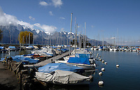 Tarpaulin covered boats moored on Lake Léman, with snow covered mountains in the background. Clarens close to Montreux Switzerland.