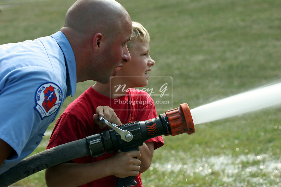 "A fire fighter helps a young boy who is holding water hose and spraying a display that is on ""fire""."