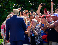 United States President Donald J. Trump greets guests prior to making remarks and answering questions as he prepares to depart the South Lawn of the White House in Washington, DC on Friday, July 5, 2019.  The President will travel to Westminster, New Jersey for the weekend.<br /> CAP/MPI/RS<br /> ©RS/MPI/Capital Pictures
