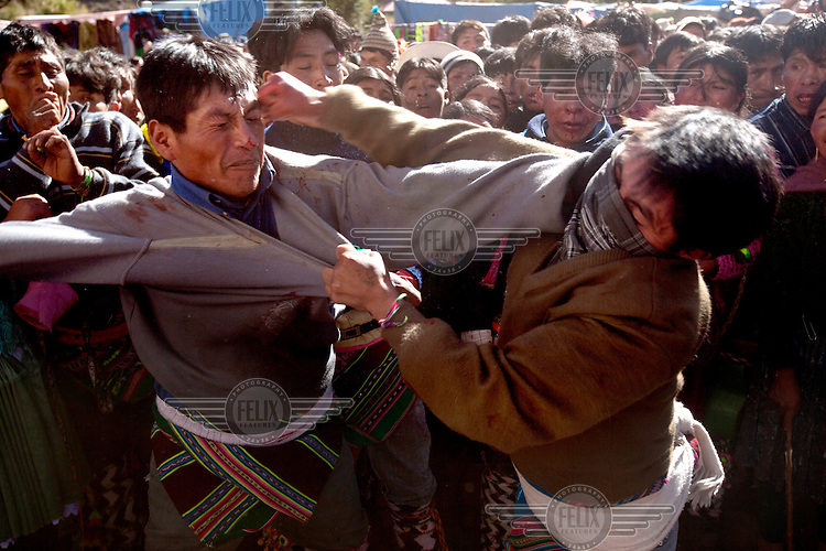 Two men punch each other during the ritual fighting in the plaza of Macha. <br /> <br /> The people of Macha and surrounding communities carry on the pre-Columbian tradition of ritual fighting. The communities gather on the plaza of Macha to fight and dance in competition with each other. The blood that is spilled is an offering to Mother Earth. In return, the people ask for rain and a good harvest. This ritual is called tinku or fiesta de la cruz since the cross is also engaged in the festivities. The cross is dressed up, given offerings and brought from communities around Macha to the church in town. This syncretic festival melds pagan, pre-christian rituals with Catholic practice. /Felix Features