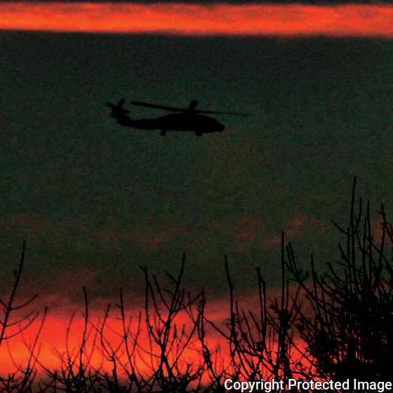 03/15/05.....Gary Wilcox/staff..... A Navy Helicopter flys over <br /> Fletcher High School at sunset last Monday night.