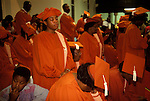 Choir members of the Calvary Church of God in Christ South London pray during a Sunday church service. A young member of the congreation his mother is in the choir looks bored. from A STORM IS PASSING OVER a Look at Black Churches in Britain. Calvary Church of  God in Christ is part of the generic term for these groups of churches who we call the  Church of God of Prophecy. Published by Thames and Hudson isbn 0 500 27826 1