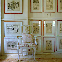 A Swedish-style painted armchair stands in front of a collection of framed prints of mechanical drawings