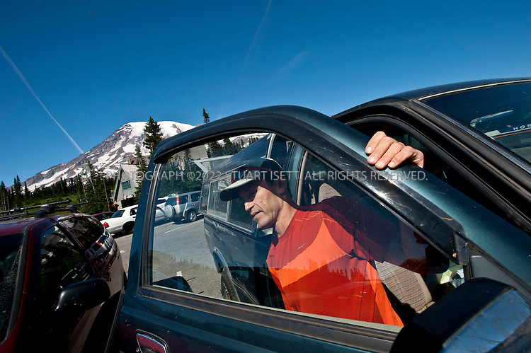 9/14/2011--Mt. Rainier, WA, USA..Climber Chad Kellogg sometimes lives out of his truck. Here at the foot of Mt. Rainier, WASH.,  he climbs out of his truck after putting on clothes for the day's training...Climber Chad Kellogg, 39, training on Mt. Rainier, WASH., for the world speed record climb on Mt. Everest that he will attempt in May, 2012. Kellogg climbs solo and without oxygen...A former competitive luger, Kellogg is a Buddhist who wakes everyday at 4 a.m. to meditate before heading out for training and work. A few years ago, Kellogg had part of his colon removed because of cancer and also lost his first wife to a climbing accident..©2011 Stuart Isett. All rights reserved.