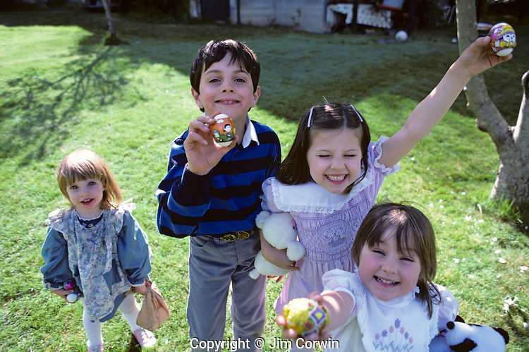 Kids, hamming it up in front of camera at Easter time, holding up Easter eggs with happy expressions, backyard in Issaquah, Washington USA  MR