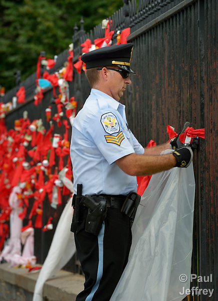 A U.S. Park Police officer removes ribbons from the White House fence on July 24, 2012. The ribbons were placed there by protestors criticizing U.S. support for pharmaceutical companies which have resisted generic licenses for their drugs for people living with HIV and AIDS. Several people were arrested after tying the ribbons, many connected to prescription bottles, to the fence. The protest took place during the XIX International AIDS Conference.