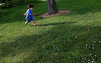 leaving0627 Christian Sanchez, 2,  plays in the grass in an Ohio rest stop while on the way to Pennsylvania.  (Pat Shannahan/ The Arizona Republic)