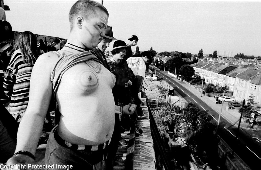 A protester taunts police and bailiffs who are preparing to evict the last squatted house on the route of the M11 motorway.<br /> July 1995.<br /> &copy;Andrew Testa