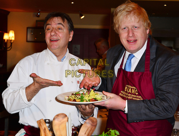 The Mayor of London, Boris Johnson, meets celebrity chef Raymond Blanc and a few of his new apprentices, as the pair encourage more businesses to establish young apprenticeships and help the Mayor to reach his target of 100,000 in the capital. Brasserie Blanc, London, England..March 6th, 2013.half length black suit white shirt apron maroon hand arm blue tie funny plate food  .CAP/BF.©Bob Fidgeon/Capital Pictures.