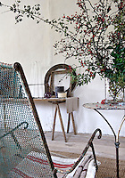 A large vase of rosehips sits on a distressed metal side table in the living room
