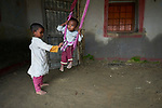 Ritika Mardi swings her baby sister Monalisa in the village of Suihari in northern Bangladesh. <br /> <br /> Parental consent obtained.
