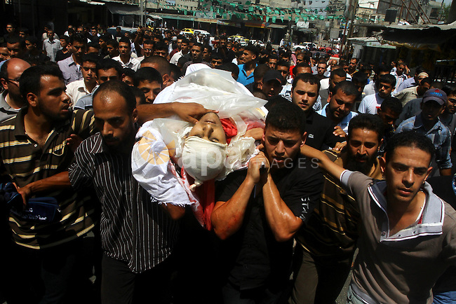 Palestinian mourners carry the body of the Popular Resistance Committees militant, Khaled Abu Samhoud, who was killed in Israeli airstrike, during his funeral in the southern Gaza Strip city of Khan Younis, Sept. 7, 2011. A Palestinian militant was killed and two others wounded when an Israeli airstrike targeted a group of gunmen in southeastern Gaza Strip on Tuesday, witnesses and security sources said. Photo by Ashraf Amra