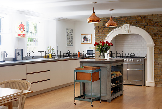 In the kitchen/dining room original features such as the tiled alcove and exposed brick wall are juxtaposed with contemporary white kitchen units