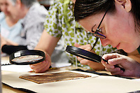 Jessica Pigza, a librarian for the New York Library's Rare Book Division, uses a magnifying glass to determine the type of leather used on a book cover during a Rare Book School summer camp book binding class held at the University of Virginia in Charlottesville, Va. The school hosts an annual summer camp for scholars and other professionals who work with rare books. Photo/Andrew Shurtleff