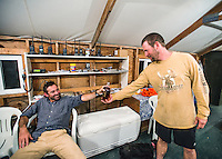 Outdoor Life Editor Andrew McKean and guide Greg Kriese with Trefren Outfitters enjoy a pot hunt toast with whisky at camp outside of Alpine, Wyoming, September 22, 2015.<br /> <br /> Photo by Matt Nager