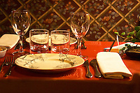 Dining table set for two with plates, glasses, silver wear, linen napkin and a red table cloth. at the gastronomic restaurant L'Enfance de Lard Bergerac Dordogne France
