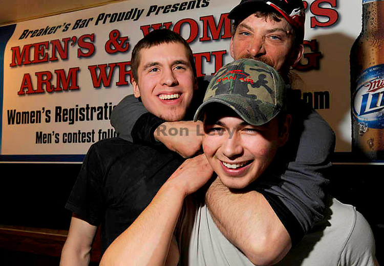 Lance Mackey holds Dale Ellaya (below( and Alex Morgan in arm locks, Arm Wrestling contest, Breaker's Bar, Nome, Alaska