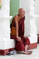 Myanmar, Burma.  Shwedagon Pagoda, Yangon, Rangoon.  Buddhist Monk Laughing.