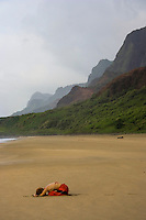 A woman does yoga at Kalalau Beach, with Na Pali coastline in the distance, Kaua'i.