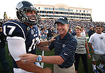 Nevada quarterback Cody Fajardo talks with former Nevada head coach Chris Ault before a pre-game ceremony renaming Mackey Stadium as Chris Ault Field, in Reno, Nev., on Saturday, Sept. 7, 2013. Kathy Ault, center, was among family and friends who participated in the ceremony. (AP Photo/Cathleen Allison)