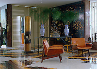 A pair of retro leather armchairs in the living area stand on a white tiled floor with a dramatic and colourful pattern
