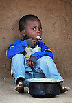 """Four-year old Matthew Dzongololo eats sorghum porridge for breakfast in Chidyamanga, a village in southern Malawi that has been hard hit by drought in recent years, leading to chronic food insecurity, especially during the """"hunger season,"""" when farmers are waiting for the harvest."""