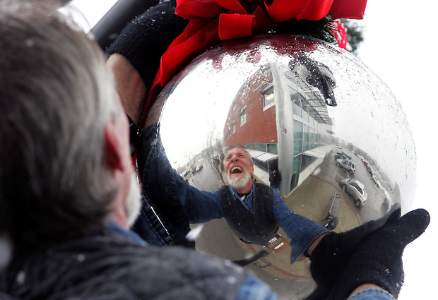 Amid falling snow, Rick Frey of Boesen The Florist removes a Christmas ornament from a lightpost along Locust Street in Des Moines' East Village.  Sixty-seven of the ornaments adorned the street from City Hall to the State Capitol during the holidays.