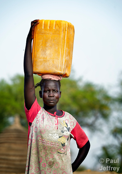 A displaced woman carries water home in Agok, a town in the contested Abyei region where tens of thousands of people fled in 2011 after an attack by soldiers and militias from the northern Republic of Sudan on most parts of Abyei. Although the 2005 Comprehensive Peace Agreement called for residents of Abyei--which sits on the border between Sudan and South Sudan--to hold a referendum on whether they wanted to align with the north or the newly independent South Sudan, the government in Khartoum and northern-backed Misseriya nomads, excluded from voting as they only live part of the year in Abyei, blocked the vote and attacked the majority Dinka Ngok population. The African Union has proposed a new peace plan, including a referendum to be held in October 2013, but it has been rejected by the Misseriya and Khartoum. The Catholic parish of Abyei, with support from Caritas South Sudan and other international church partners, has maintained its pastoral presence among the displaced and assisted them with food, shelter, and other relief supplies.