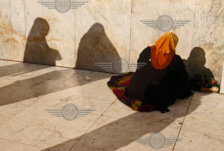Woman and silhouettes outside the Mosque of Saiyidna Hussein.