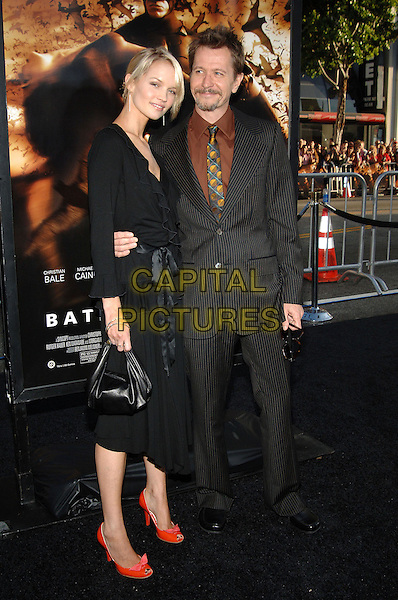 "ALISA MARSHALL & GARY OLDMAN.""Batman Begins"" Los Angeles Premiere held at Grauman's Chinese Theatre, Hollywood, CA.June 6th, 2005.Photo credit: Jacqui Wong/AdMedia.full length arm around waist orange shoes heels black pinstripe suit black purse black dress.www.capitalpictures.com.sales@capitalpictures.com.© Capital Pictures."