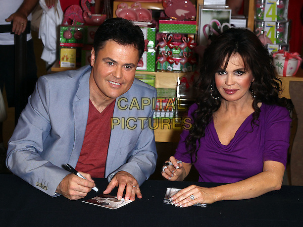 "Donny Osmond & Marie Osmond.Donny and Marie celebrate release of ""Donny  & Marie"" with album signing at Flamingo Las Vegas, Las Vegas, Nevada, USA, 21st June 2011..half length family brother sister sitting  top blue blazer jacket red v-neck t-shirt purple .CAP/ADM/MJT.© MJT/AdMedia/Capital Pictures."