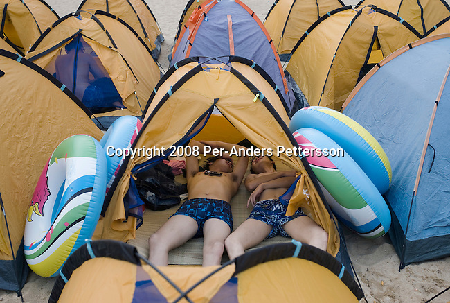 SHENZHEN, CHINA OCTOBER 2: Young men rest in their rented tent on Dameisha Beach Park on October 2, 2008 outside Shenzhen, China. Millions of Chinese took a weeklong break during the National Holiday and one of the Golden weeks during the year. This is the most popular beach outside Shenzhen, and it's free. The park also has carnival rides and a statue park. Chinese people love theme parks and new ones are opening constantly. It's estimated that there's about 2400 theme parks in the country. Many of the most popular parks are located around Shenzhen and over the border in Hong Kong. (Photo by Per-Anders Pettersson).