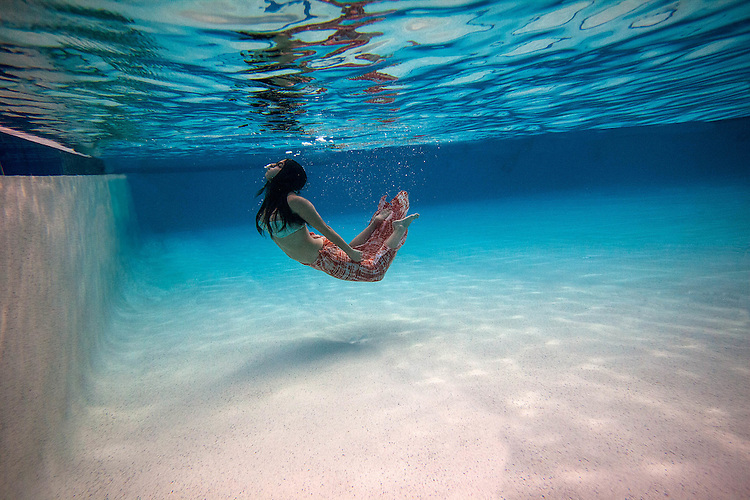 Young Woman posing underwater in a pool