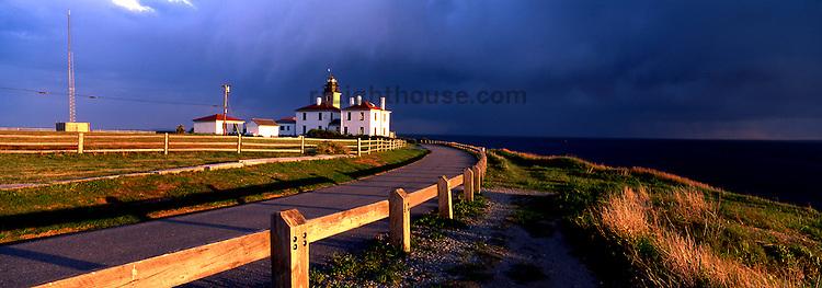 The setting sun illuminates the Beavertail Lighthouse.