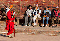 Nepal, Patan.  A Hindu Sadhu (Holy Man) Walks Past Men and One Woman Resting on Bench in Durbar Square.  The  trident that the sadhu carries marks him as a devotee of Shiva.