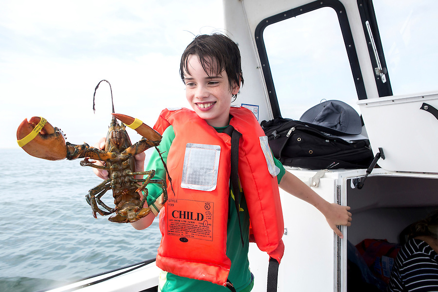 A boy holds a lobster on a boat in Chatham, MA.