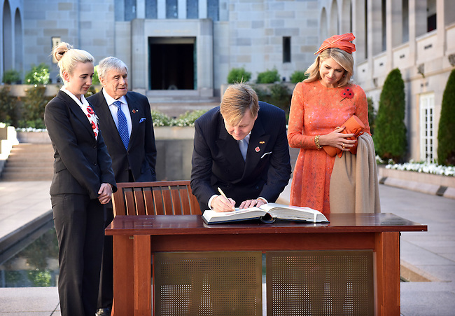 King Willem Alexander (C) and Queen Maxima (R) of the Netherlands sign the visitors book during a visit to the Australian War Memorial, Canberra, Nov 2, 2016. AFP PHOTO/ MARK GRAHAM