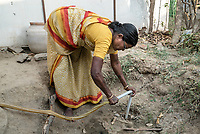 A local resident fixes a pipe into the municipal water connection in Ambedkar Nagar in Medak, Telangana, India.