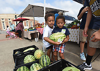 NWA Democrat-Gazette/FLIP PUTTHOFF<br /> APPRECIATED CUSTOMERS<br /> Sarah Widger, 4 (left), and her brother, Javier Widger, 3, lift a melon Saturday Aug. 12 2017 during customer appreciation day at the Springdale Farmers Market at the Jones Center for Families. Customers received free seed packets, samples of vendor items and drawings for prizes, including a cedar chair built and donated by Jack Ledbetter, a market vendor. The market is open Tuesday, Thursday and Saturday from 7 a.m. to 1 p.m. at the Jones Center. Sarah and Javier were at the market with their mom, Jamie Widger of Springdale.