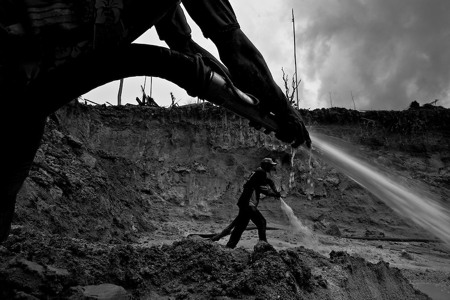 """Gold mining in Amazon rain forest. Hydraulic mining known as """"chupadeira system"""", a form of mining that uses high-pressure jets of water to dislodge rock material or move sediment. Agua Branca gold mining village, Para State, Brazil."""